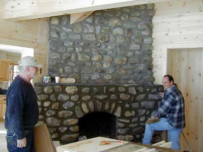 Picture of the project masons working on fireplace details.